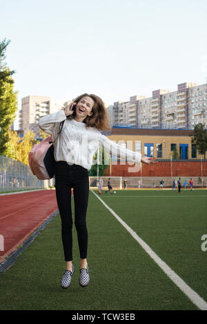 Happy high school student received good news on phone. She is dressed in a free style and jumps for joy on the football field during a telephone conve - Stock Image