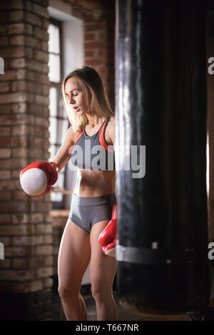 An athletic woman in boxers gloves standing near the punching bag in the gym - Stock Image