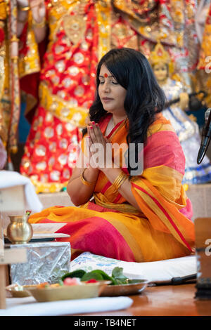 A beautiful Hindu priestess prays & meditates while leading a prayer service at a temple in Jamaica, Queens, New York. - Stock Image