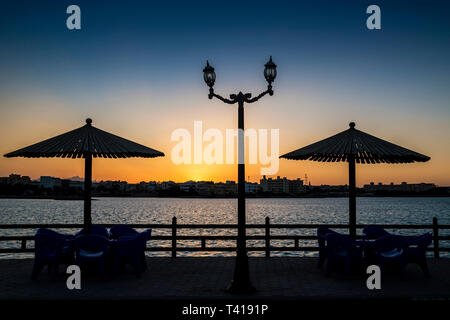 Silhouette of parasols over table and chairs in the park, Hurghada, Egypt - Stock Image