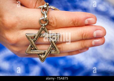 A hand of a young woman holding a key chain with a Star of David, traditional Jewish symbol. Concept image for the international Holocaust remembrance - Stock Image