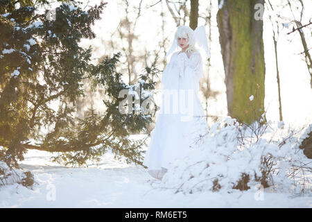 Beautiful blonde girl stands in snowy forest in image of good angel with wings dressed in white clothing. - Stock Image
