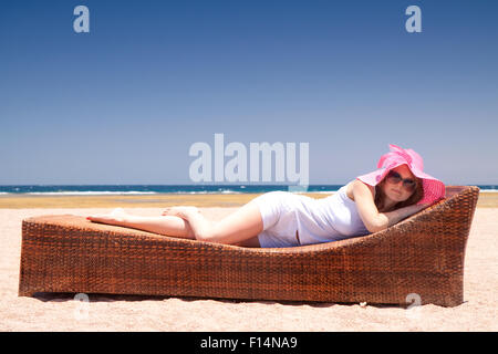 Pretty woman in a hat relaxes on a lounger on the beach - Stock Image