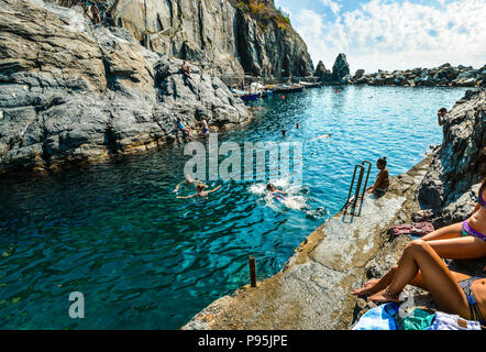 A woman dives into the swimming bay at the Cinque Terre village of Manarola, Italy - Stock Image