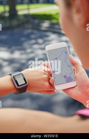 Woman wearing sports watch and holding smartphone. - Stock Image