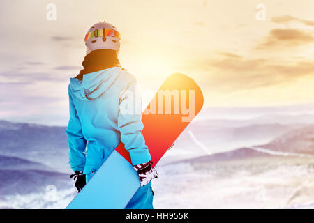 Snowboarder woman girl sunrise mountain top - Stock Image