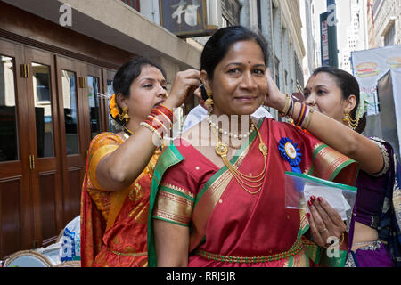 An Indian woman has her hair and jewelry adjusted by two friends just prior to the India Day Parade in Manhattan, New York City. - Stock Image