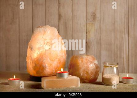 Himalayan Salt Soap bar, pink rock salt lamp turned on and salt candle holder, with candle burning inside, jar with salt grains on light bokeh backgro - Stock Image