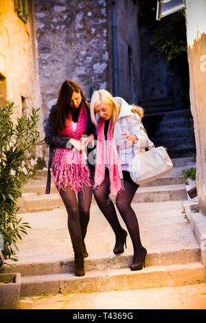 Drunk teenage stumblin'in drunk teen girls laugh walking walk front frontal view full length intoxicated attractive females stiletto shoes - Stock Image