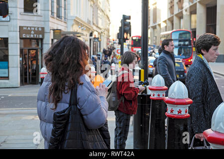 A view of woman texting on phone in crowd waiting for traffic lights on Cannon Street in the City of London England UK  Europe KATHY DEWITT - Stock Image