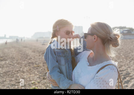 Mother and daughter wearing sunglasses on sunny beach - Stock Image