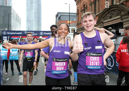 Competitors celebrate after completing the Simply Health Manchester Run. - Stock Image