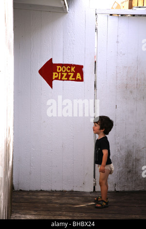 Boy looking in the direction of a pizza restaurant sign, Fair Harbor, Fire Island, NY, USA - Stock Image