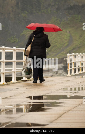 Aberystwyth Wales UK, Tuesday 16 April 2019.  UK Weather : A woman walking under a red umbrella along the promenade on a dull and damp but mild day at the seaside in Aberystwyth Wales as the Easter school holidays get into swing. Photo credit Keith Morris / Alamy Live News - Stock Image