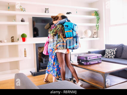 Young women friends hugging, arriving at house rental - Stock Image