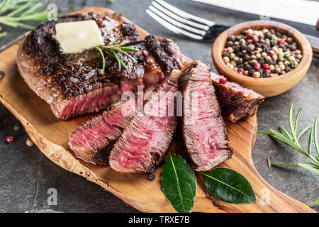 Medium rare Ribeye steak with herbs and a piece of butter on the wooden tray. - Stock Image