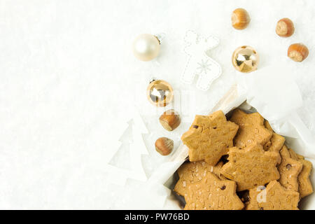 Christmas shortbread cookies with hazelnuts in star shape in wooden box. White ornaments fir tree deer golden balls on snowy background. Holiday bakin - Stock Image