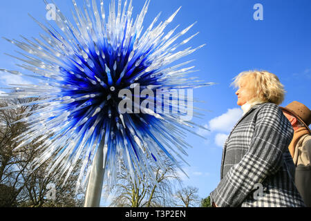 Kew Gardens, Richmond, London, UK. 11th Apr, 2019. Visitors admire the blue and white 'Sapphire Star' installation. Celebrated contemporary glass artist Dale Chihuly brings his work to the stunning backdrop of UNESCO world heritage site Kew Gardens, in a major exhibition of installations that respond to Kew's architectural and horticultural glory. The exhibition features 32 artworks in 13 locations, and runs from Saturday 13 April to Sunday 27 October 2019. Credit: Imageplotter/Alamy Live News - Stock Image