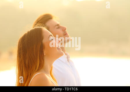 Side view portrait of a happy couple on the beach breathing deep fresh air at sunset - Stock Image