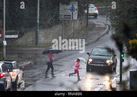 Chippenham, Wiltshire, UK. 18th Feb, 2019. A woman and a young girl using umbrellas to protect themselves from the heavy rain are pictured using a pedestrian crossing in Chippenham as heavy rain showers make their way across Southern England. Credit: lynchpics/Alamy Live News - Stock Image