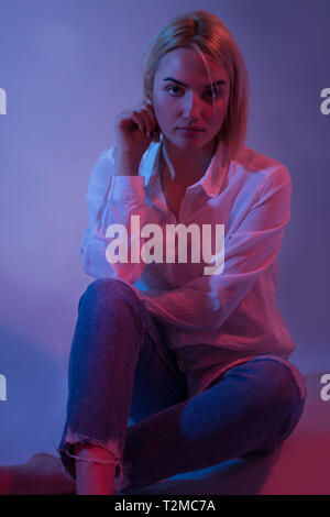 Sexy young woman portrait, on colorful background. Seductive blonde model girl in blue jeans. Girl sitting down. Red and blue light. Night life - Stock Image