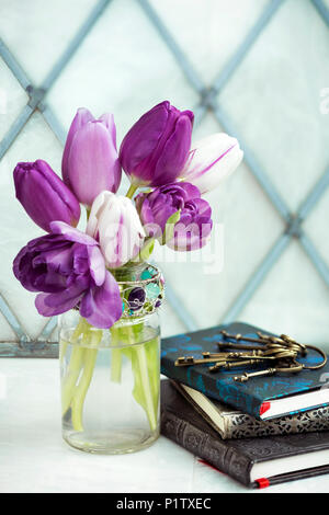 Cut tulips in a decorative glass jar with a pile of books and vintage keys - Stock Image