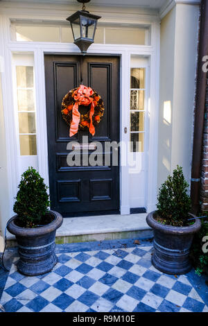 Christmas holiday wreaths decorate a wooden door on a historic home during the holidays on Lagare Street in Charleston, South Carolina. - Stock Image