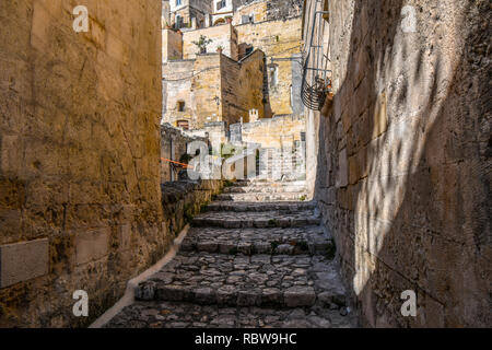 A cat walks through a narrow alley with stairs in a residential district filled with abandoned buildings near the Sassi in the city of Matera, Italy - Stock Image