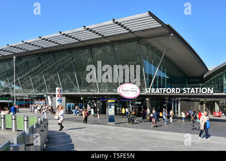 People at entrance & front glass building facade of Stratford public transport train railway station welcome to Newham sign East London England UK - Stock Image