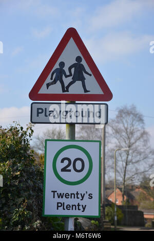 20 is plenty sign and playground sign in the north Oxfordshire village of Hook Norton, a warning for traffic to - Stock Image