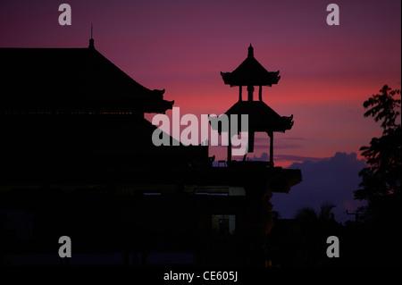 Hindu temple silhouetted in dusk sky, Ubud Bali Indonesia - Stock Image