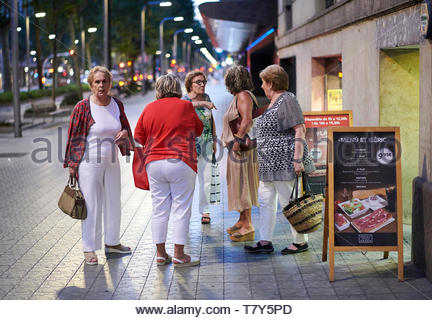 Women talking outside a cafe at night on the  Street in the City of Barcelona in Catalunya in Spain in Europe - Stock Image