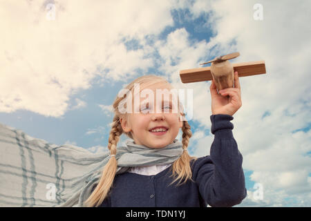 Traveling and freedom concept. Girl in blue jacket and airplane - Stock Image