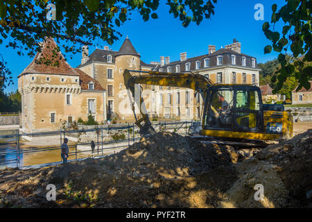 Digger scooping earth and rocks during repair to moat wall, Chateau Boussay, France. - Stock Image