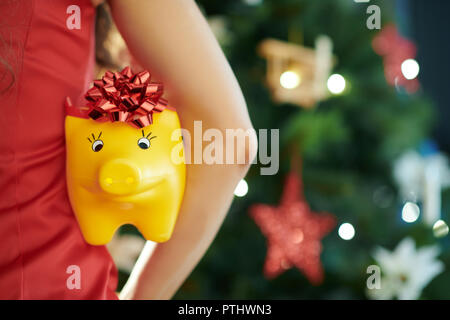 yellow piggy bank with red bow in hand of woman in red dress near Christmas tree holded by woman - Stock Image