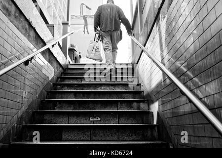 Older man walking up the subway steps with a shopping bag. - Stock Image