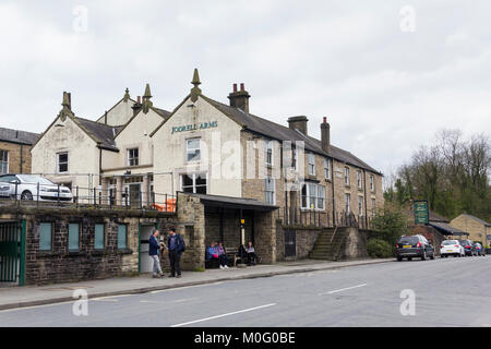 Jodrell Arms and passengers waiting at the bus shelter on Buxton Road, Whaley Bridge, Derbyshire. - Stock Image