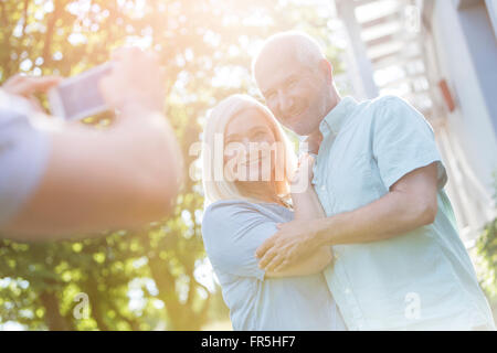 Man photographing senior couple outdoors - Stock Image