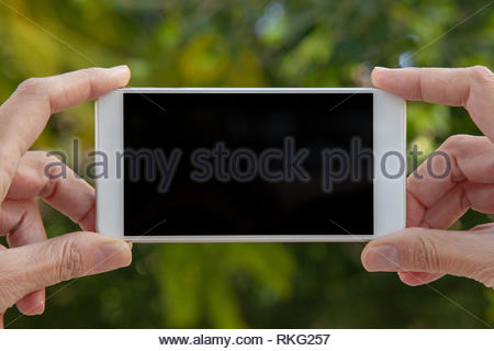 Feminine hands hold a white mobile with the empty screen in a horizontal position in an external location. - Stock Image