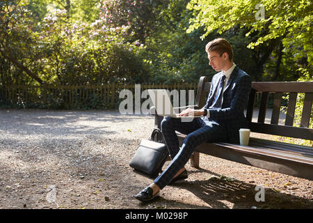 Young businessman using laptop on park bench - Stock Image