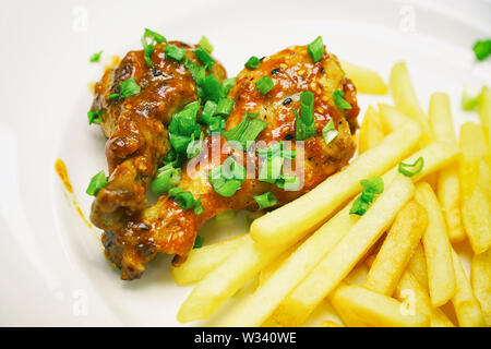 Chicken legs with french fries potatoes in a white plate - Stock Image