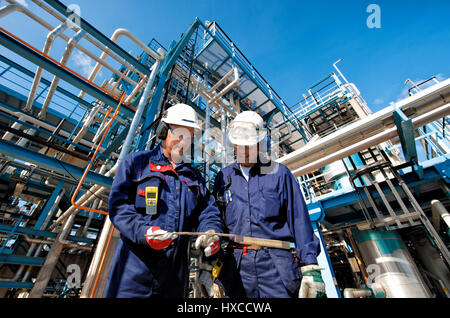 two refinery workers with large pipelines construction in background - Stock Image