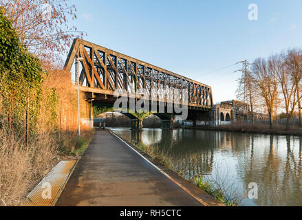 Path beside River Nene in central Peterborough, Cambridgeshire, with 19th century cast iron railway bridge, still in use on the East Coast Mainline - Stock Image