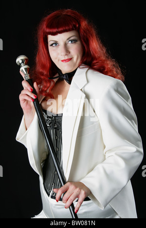 Young Red Headed Burlesque Performer  Wearing a White Coat, Bow-tie and Basque and Holding a Cane. - Stock Image