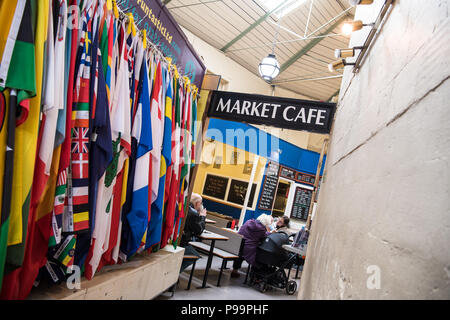 A wall full of international flags hanging from a stall at The Guildhall Market near the cate in UNESCO World Heritage site Bath, UK - Stock Image