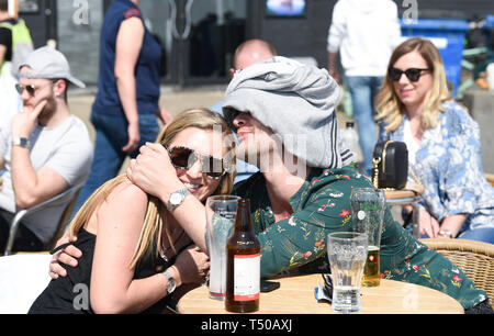Brighton, UK. 19th Apr, 2019. This chap tries to keep the sun off his head as visitors flock to Brighton beach to enjoy the Good Friday sunshine as temperatures reach the mid twenties along the South Coast Credit: Simon Dack/Alamy Live News - Stock Image