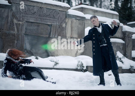 Battle of dark and light magicians with the help of magic wands and green beam on the snow background. - Stock Image