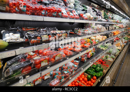vegetables like tomatoes on a shelf in a supermarket - Stock Image