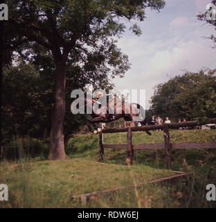 1960s, Burghley Horse Trials, cross-country event.....a male competitor on horse jumping an obstacle on the woodland course. This annual three-day event is one of the premier equestrian events in the world and the longest continuous running international event. - Stock Image