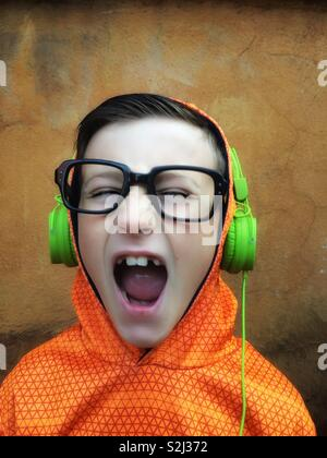 Young boy with black glasses listening and singing to music on stereo headphones - Stock Image